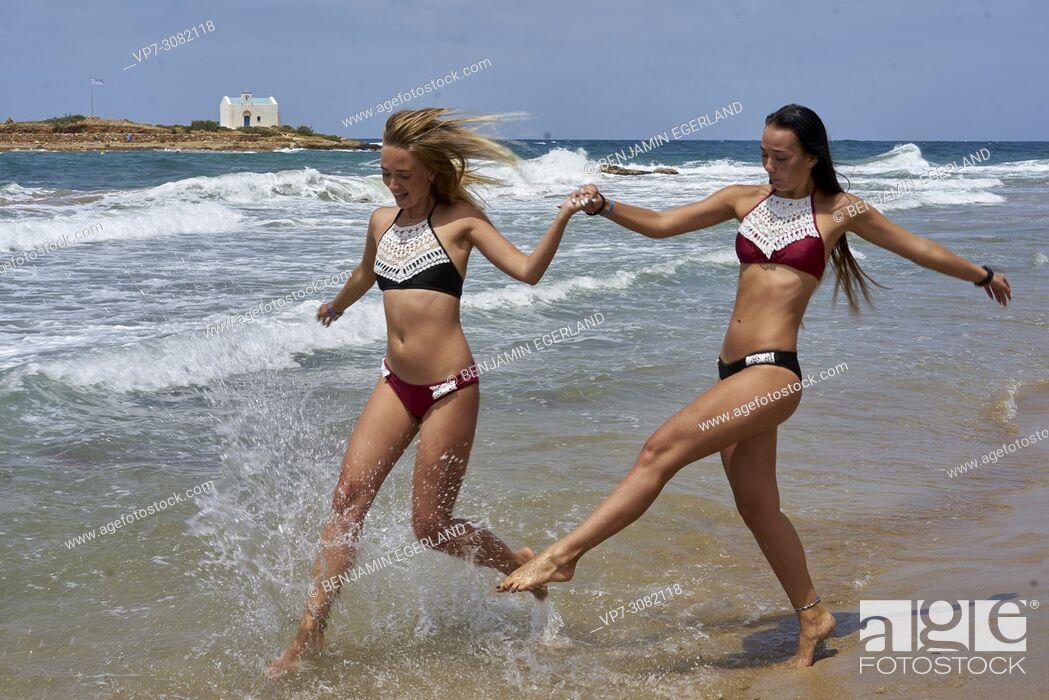 Stock Photo: two women running at beach in sea water, wearing bikini. Having fun. Holiday location Greece, Crete, Malia.