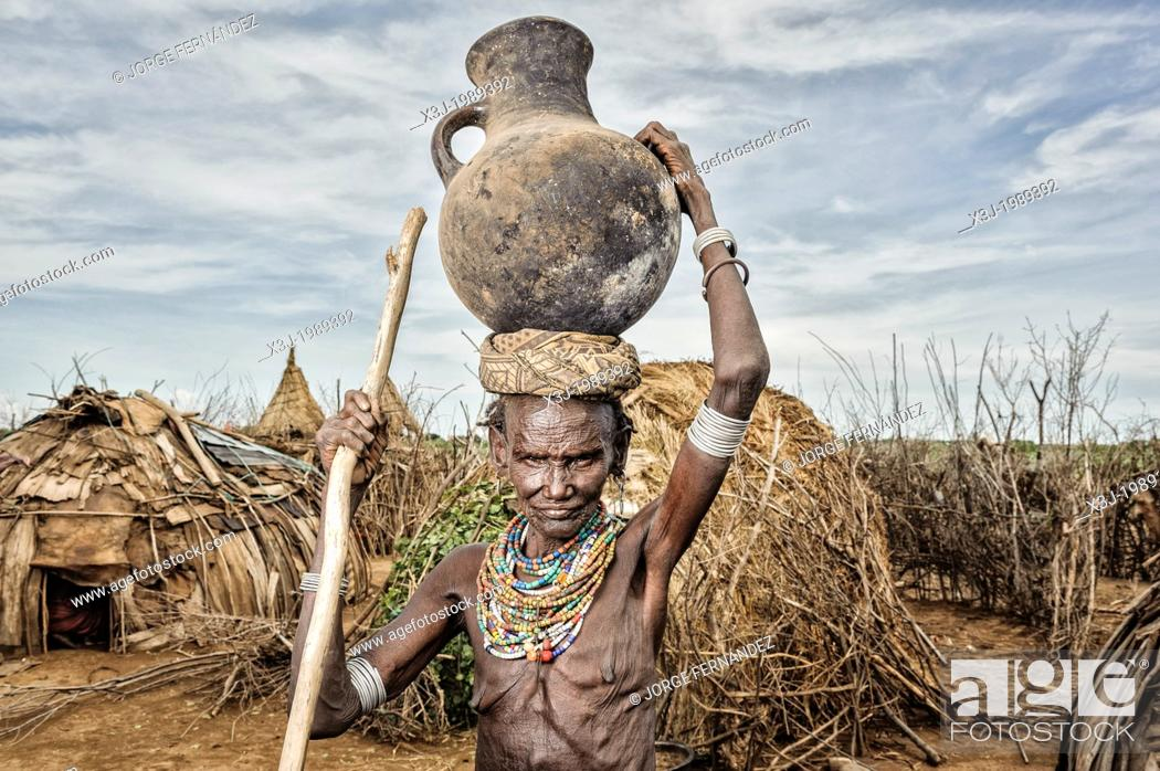 Stock Photo: Old Dassanech woman carrying a big pot over her head near Omo river, Omorate, Ethiopia.