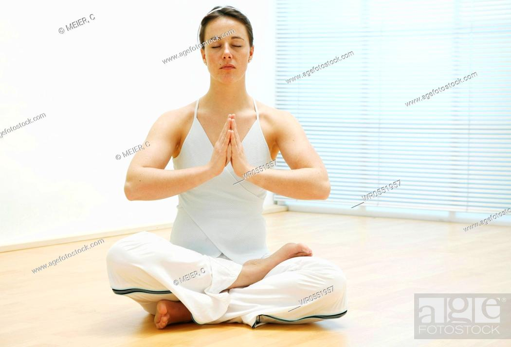 Imagen: young woman sitting on the floor and is meditating.