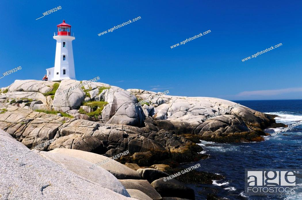 Stock Photo: Peggys Cove Nova Scotia lighthouse on smooth granite rocks with accordian player and surf.