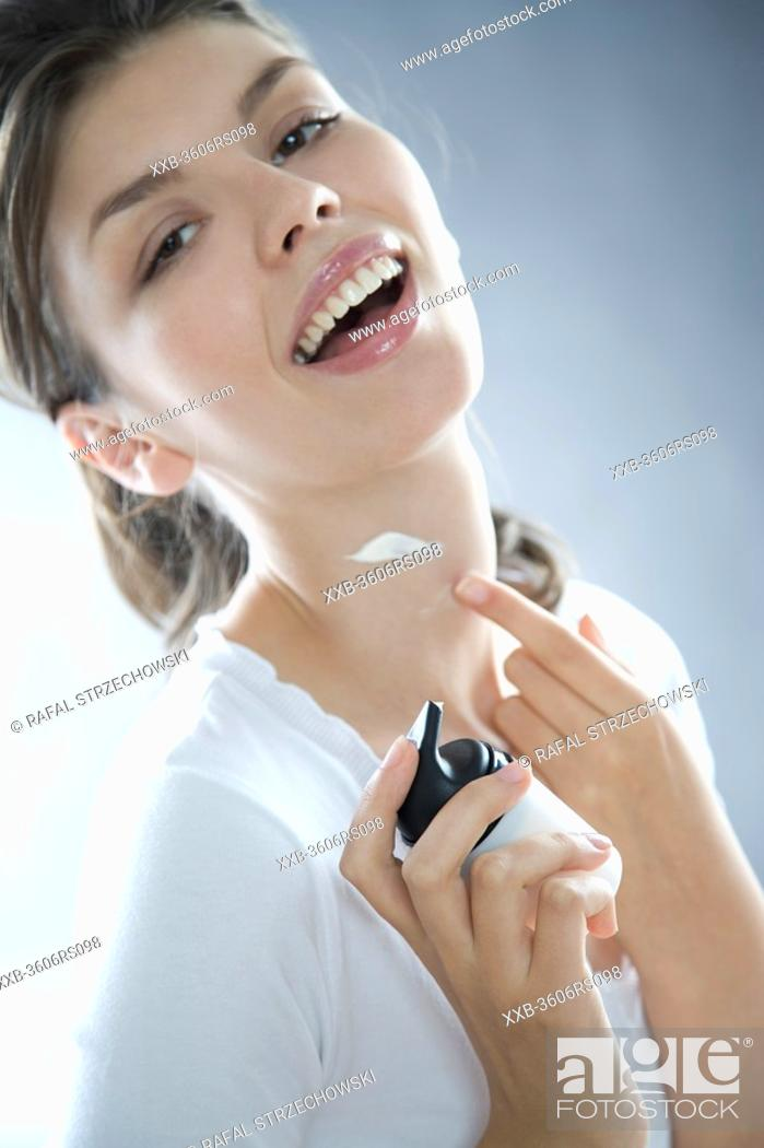 Stock Photo: young woman creaming neck.