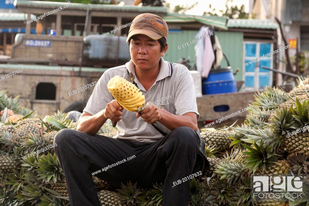 Stock Photo: Man cutting a pineapple in the floating market at Cai Rang near Can Tho.