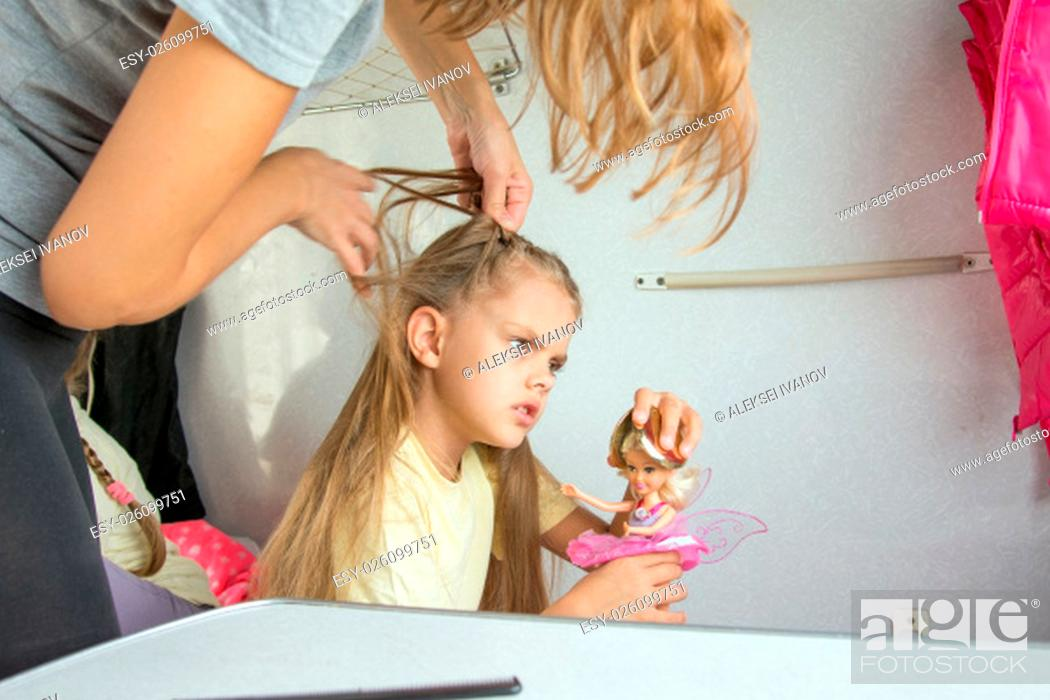 Stock Photo: Six year old girl playing in the doll while mom pigtail braids of hair, in the second-class train carriage.