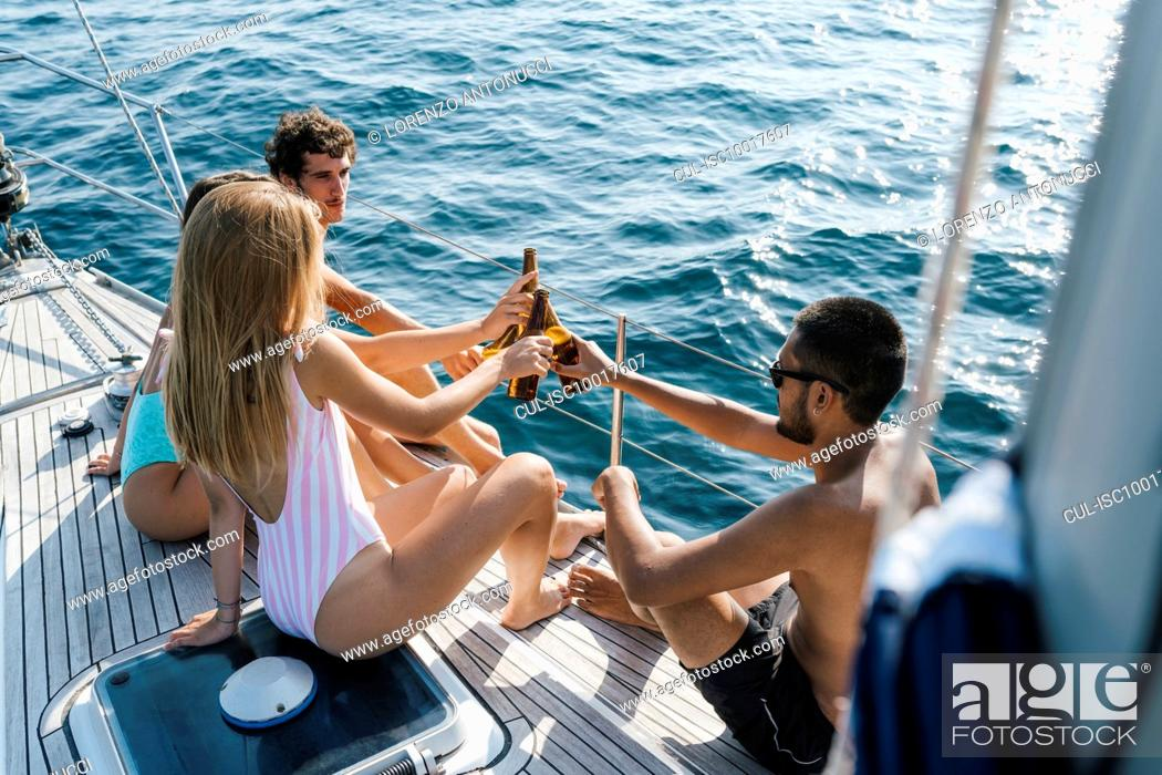 Imagen: Friends toasting with beer on sailboat, Italy.