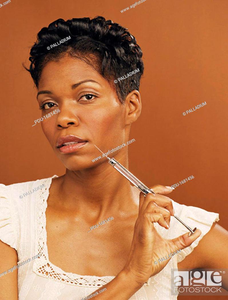 Stock Photo: Woman Holding Hypodermic Needle.