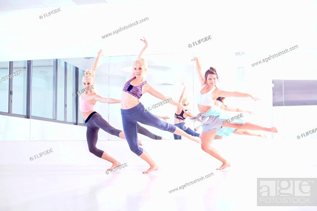 Stock Photo: Young female ballet dancers practicing in dance studio, dancing on one leg.