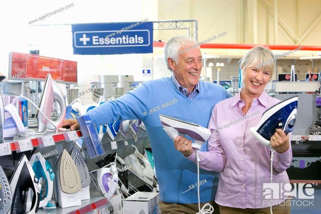 Stock Photo: Mature couple shopping for iron, smiling.