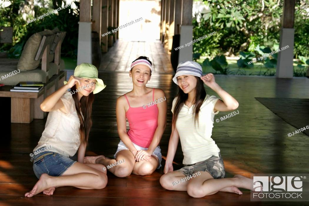 Stock Photo: View of young women sitting and smiling.