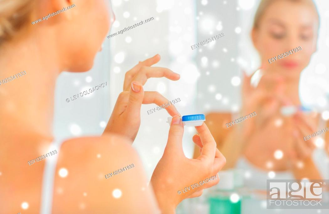 Stock Photo: beauty, vision, eyesight, ophthalmology and people concept - close up of young woman applying contact lenses at mirror in home bathroom over snow.