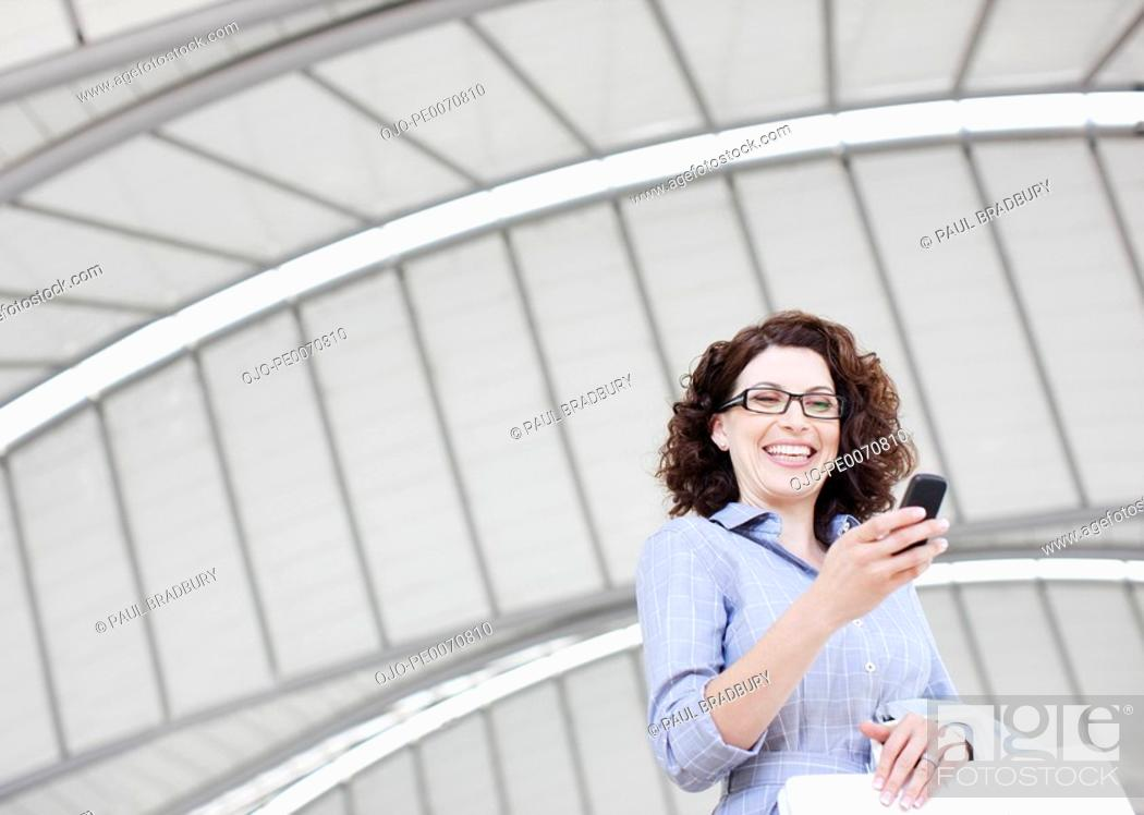 Stock Photo: Businesswoman text messaging on cell phone.