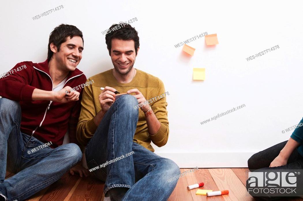 Stock Photo: Men and women sitting, men writing on adhesive note.
