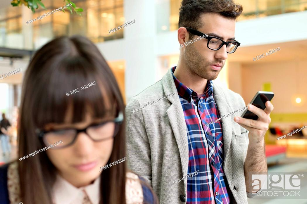 Stock Photo: Fashion designer text messaging on a mobile phone in an office.