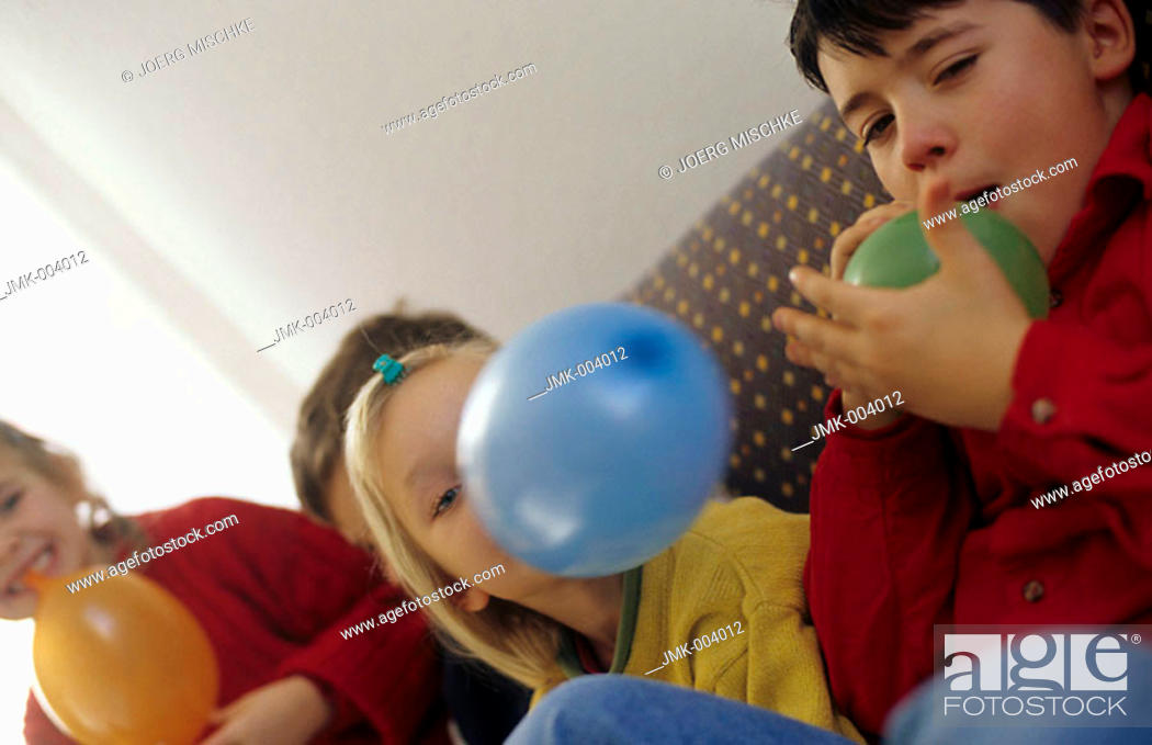 Stock Photo: Four children, boys and girls, 5-10 years old, sitting on a sofa, inflating balloons.