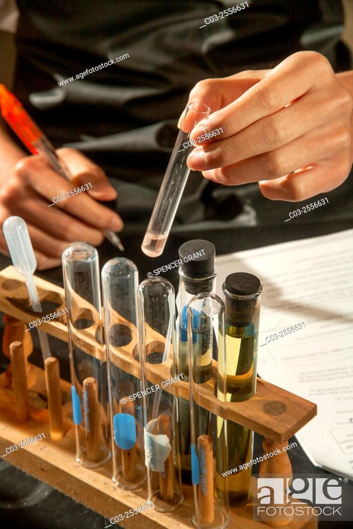 Stock Photo: A San Clemente, CA, high school chemistry student practices qualitative analysis looking for pH color change in presence of ion precipitate forming to indicate.