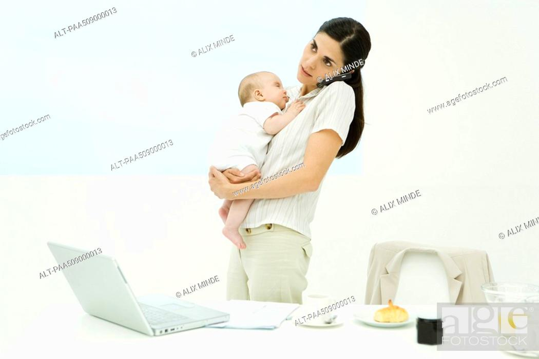 Stock Photo: Professional woman standing at breakfast table, holding baby, using cell phone.