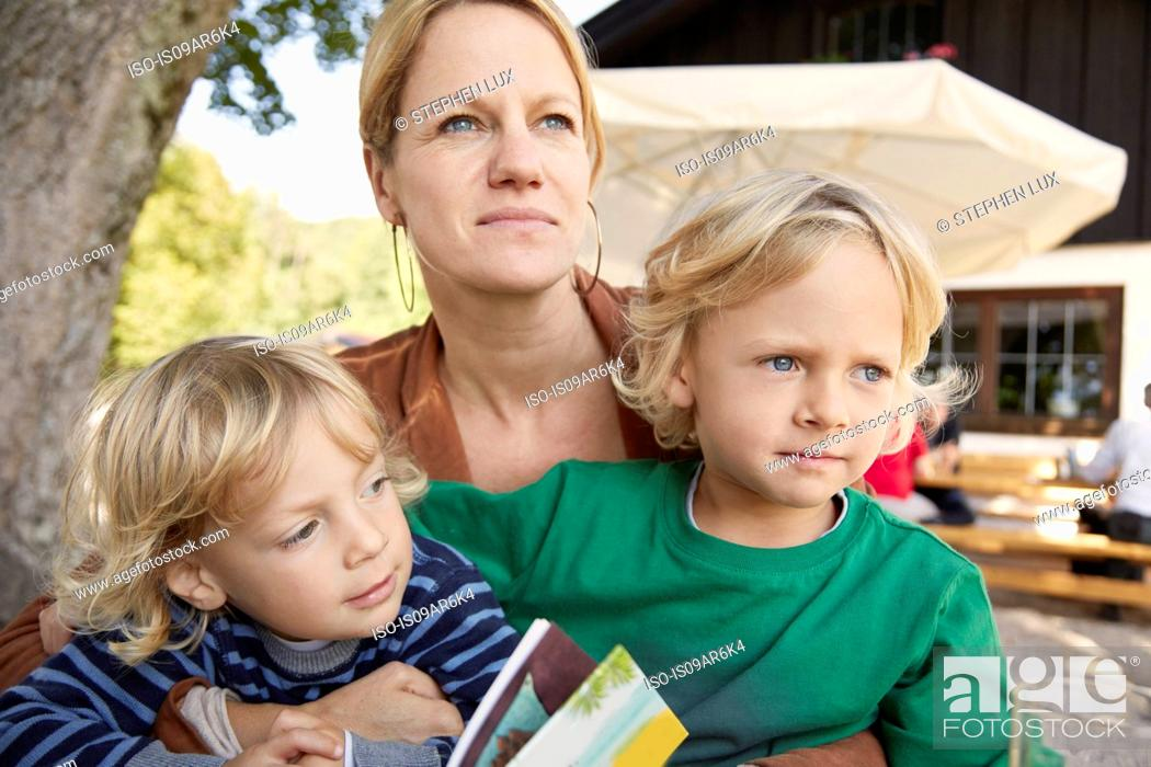 Stock Photo: Mother and two sons sitting together, outdoors.