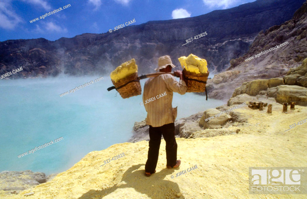 Stock Photo: Miner with heavy load of yellow elemental sulphur collected from within the active crater of Volcano Ijen, eastern Java, Indonesia.