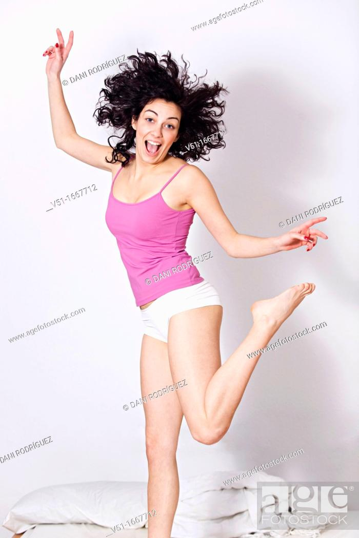 Stock Photo: Content brunette woman jumping on the bed.