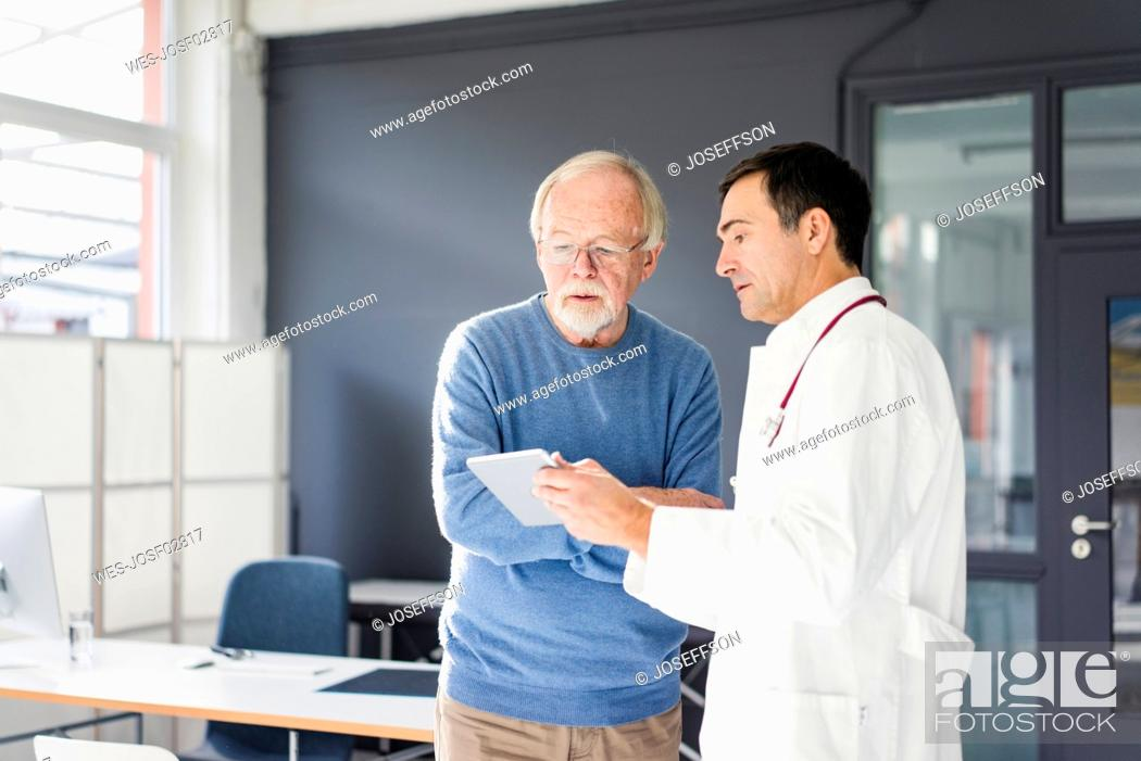 Stock Photo: Doctor showing tablet to patient in medical practice.