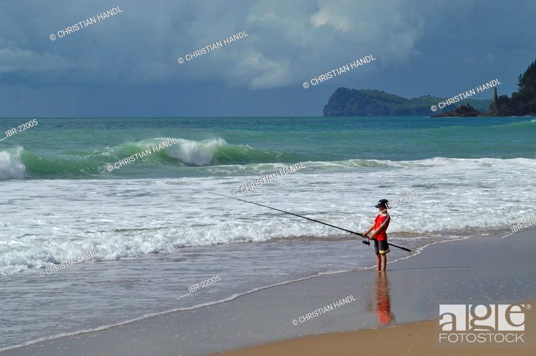 Stock Photo: Fishing kid in Cathedral Cove on Coromandel Peninsula New Zealand.