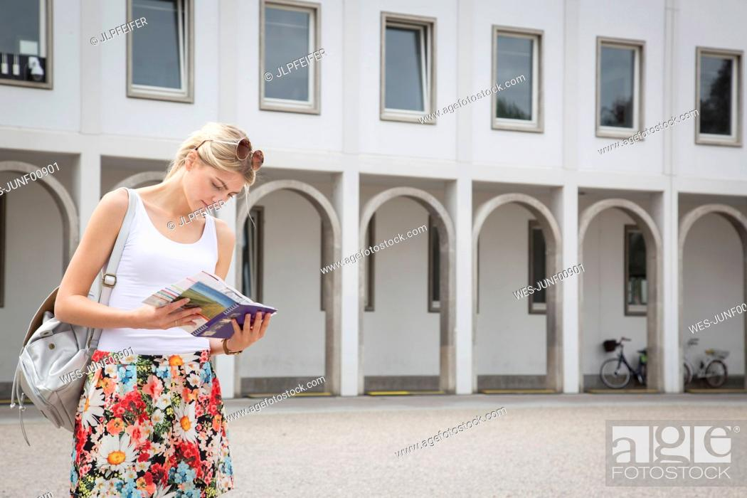 Stock Photo: Germany, Karlsruhe, tourist looking at tour guide.