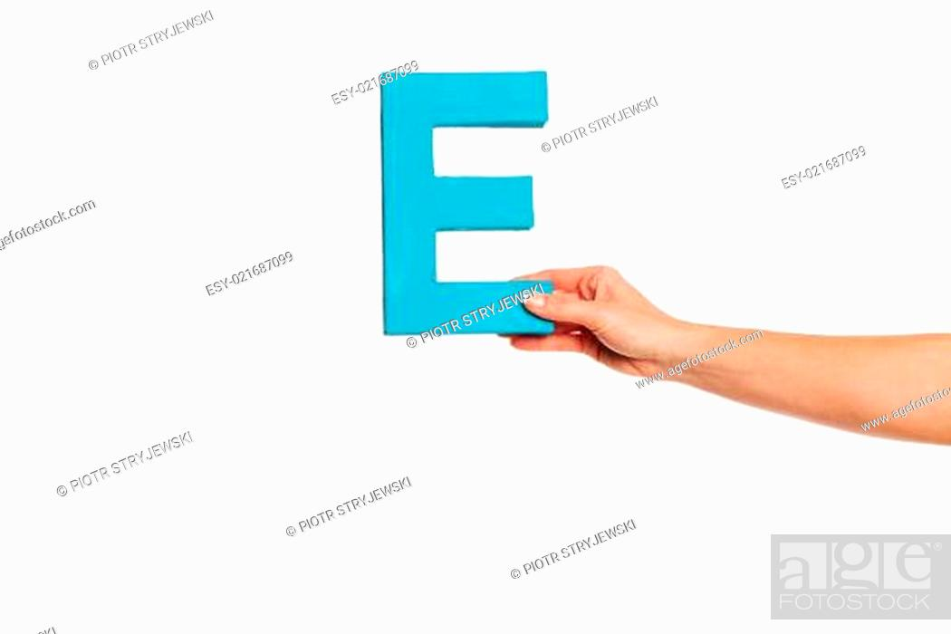 Stock Photo: hand holding up the letter E from the right.