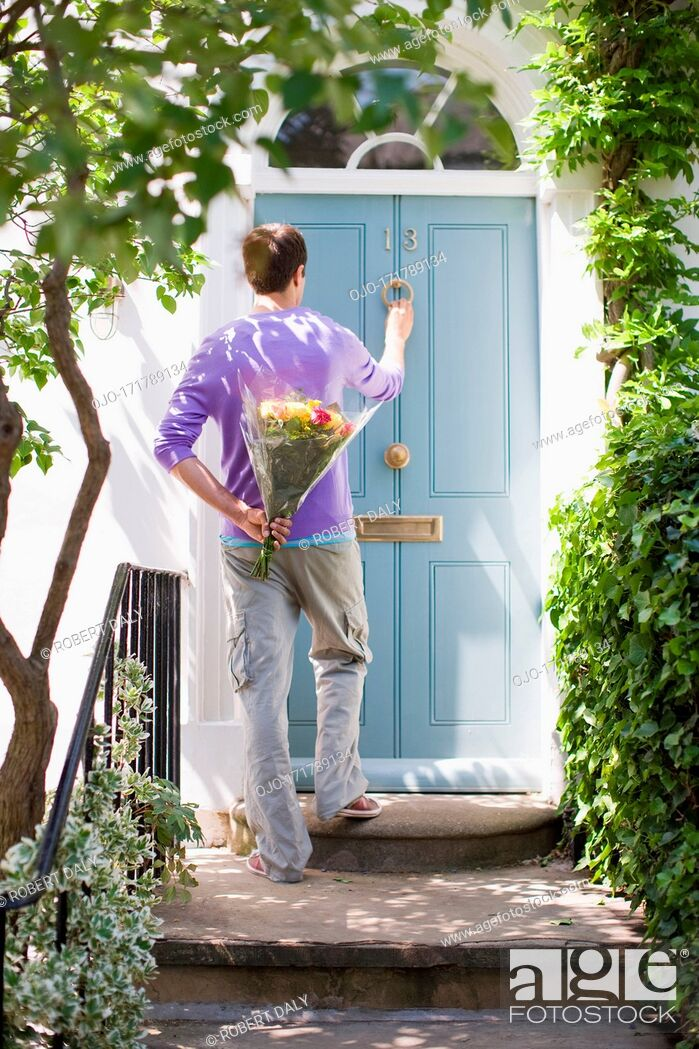 Stock Photo: Man holding bouquet of flowers and knocking on door.