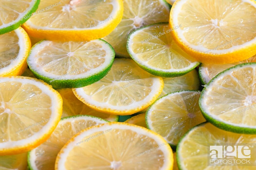 Stock Photo: Fresh green and yellow lemon slices background.