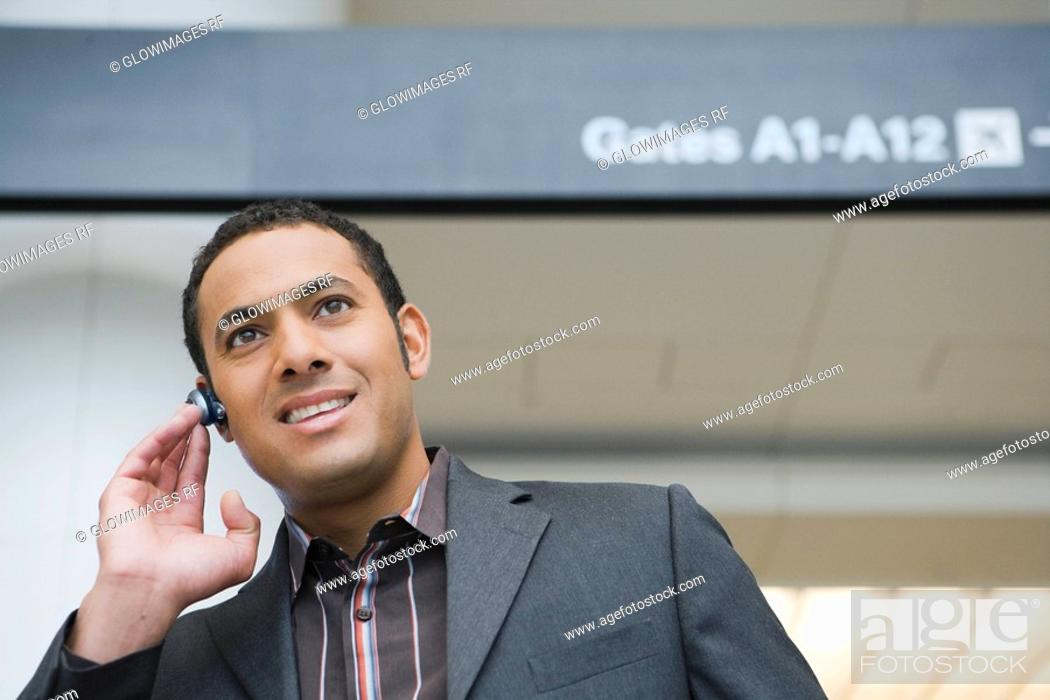 Stock Photo: Businessman talking on a hands free device at an airport.