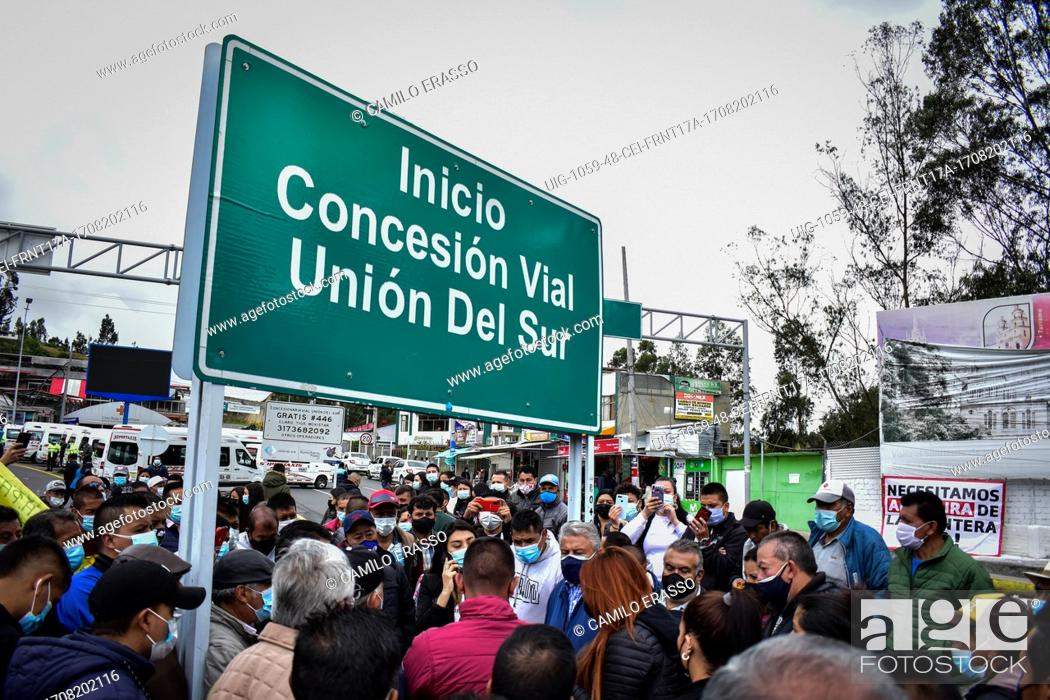 """Stock Photo: A street sign that reads """"""""Road concession of Southern Union"""""""" as drivers of public service vehicles hold protest on the Rumichaca International bridge that."""