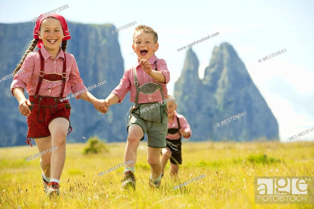 Stock Photo: Italy, Seiseralm, Three children 4-5, 6-7, 8-9 running in field.