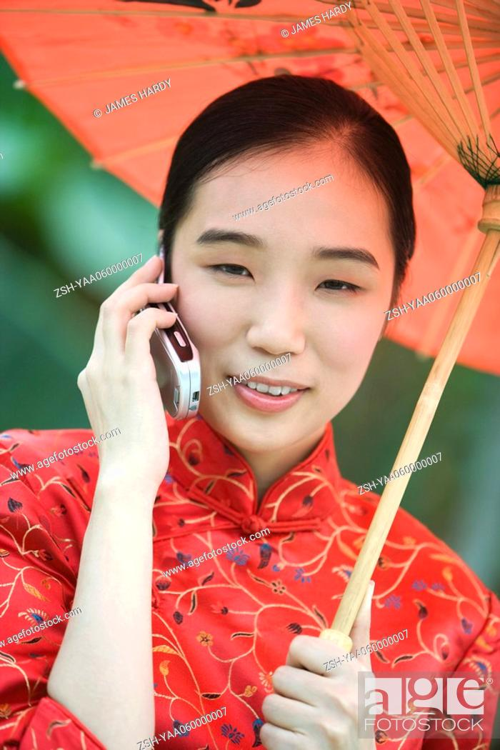 Stock Photo: Young woman dressed in traditional Chinese clothing holding parasol and using cell phone.