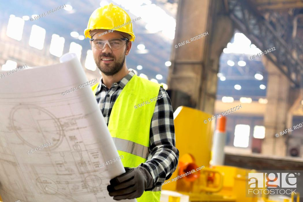 Stock Photo: Portrait smiling engineer with blueprints ins steel factory.