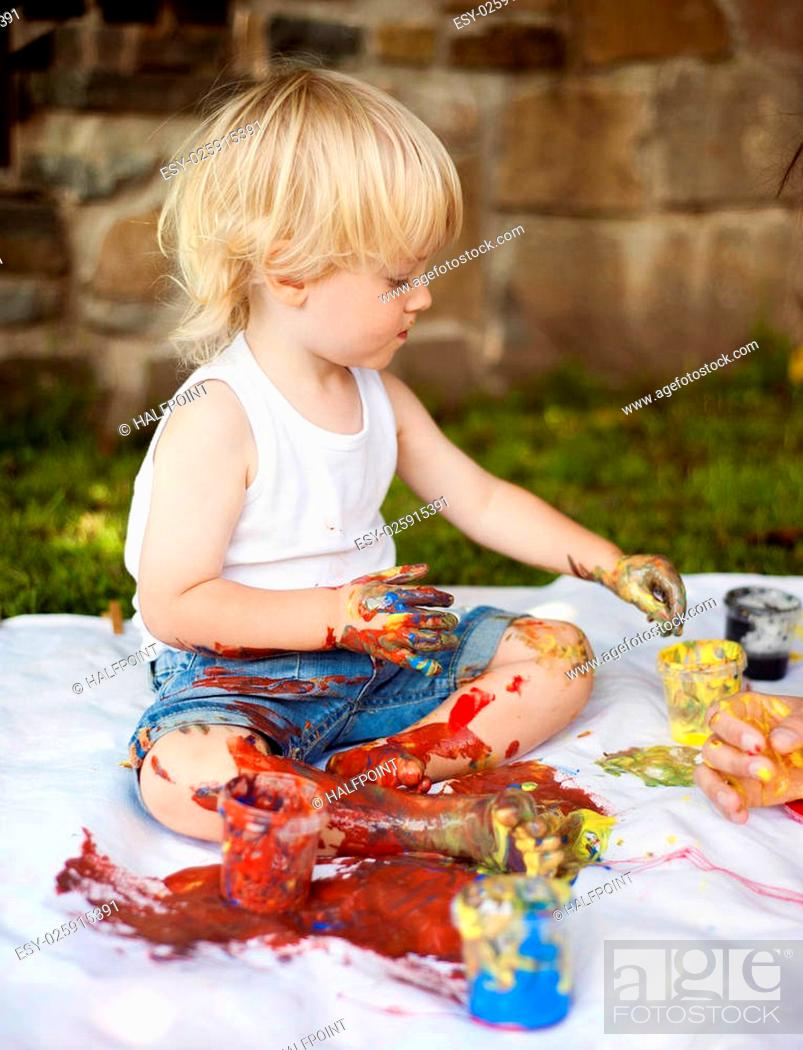 Imagen: Cute child painting with vibrant colors in the garden.