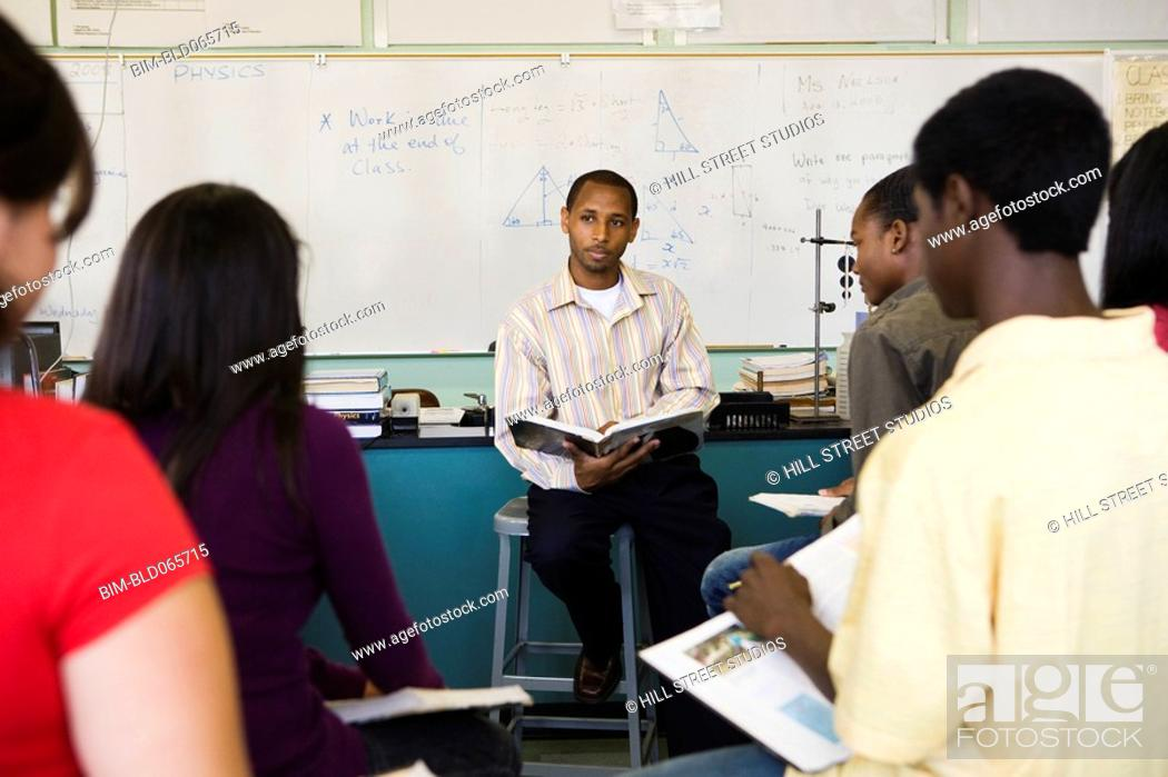Stock Photo: African teacher teaching students in chemistry lab.
