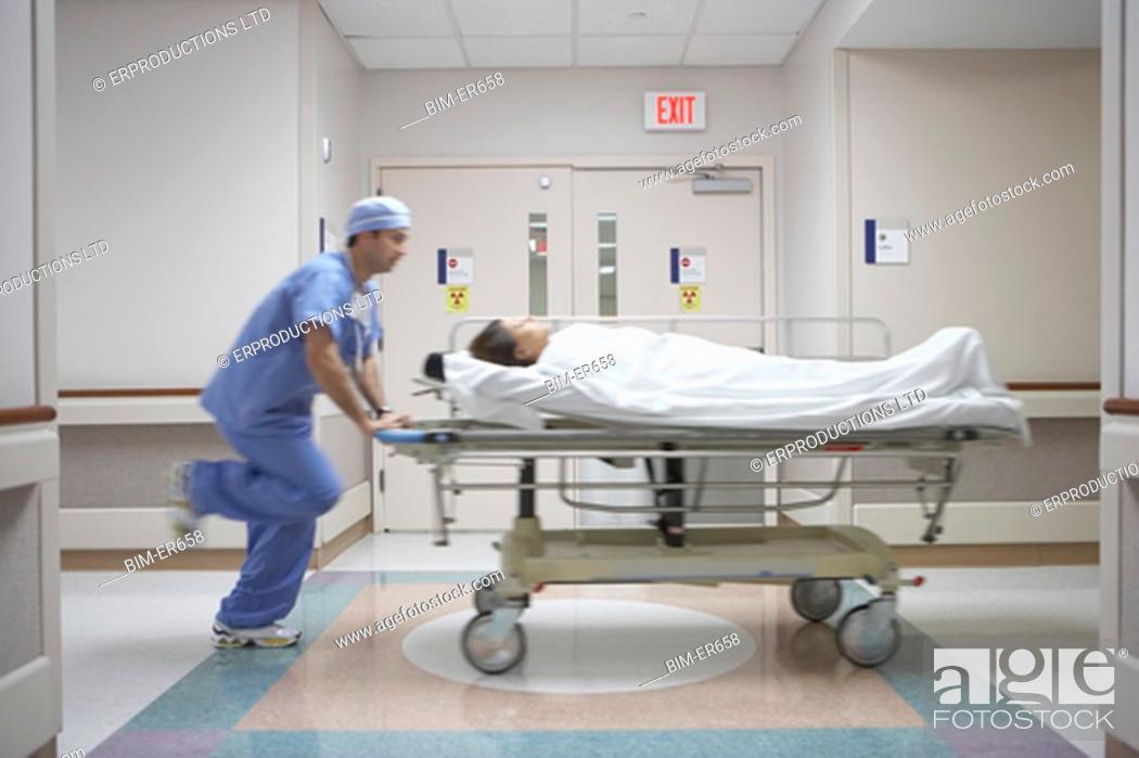 Stock Photo: Blurred motion shot of nurse wheeling gurney in hospital.