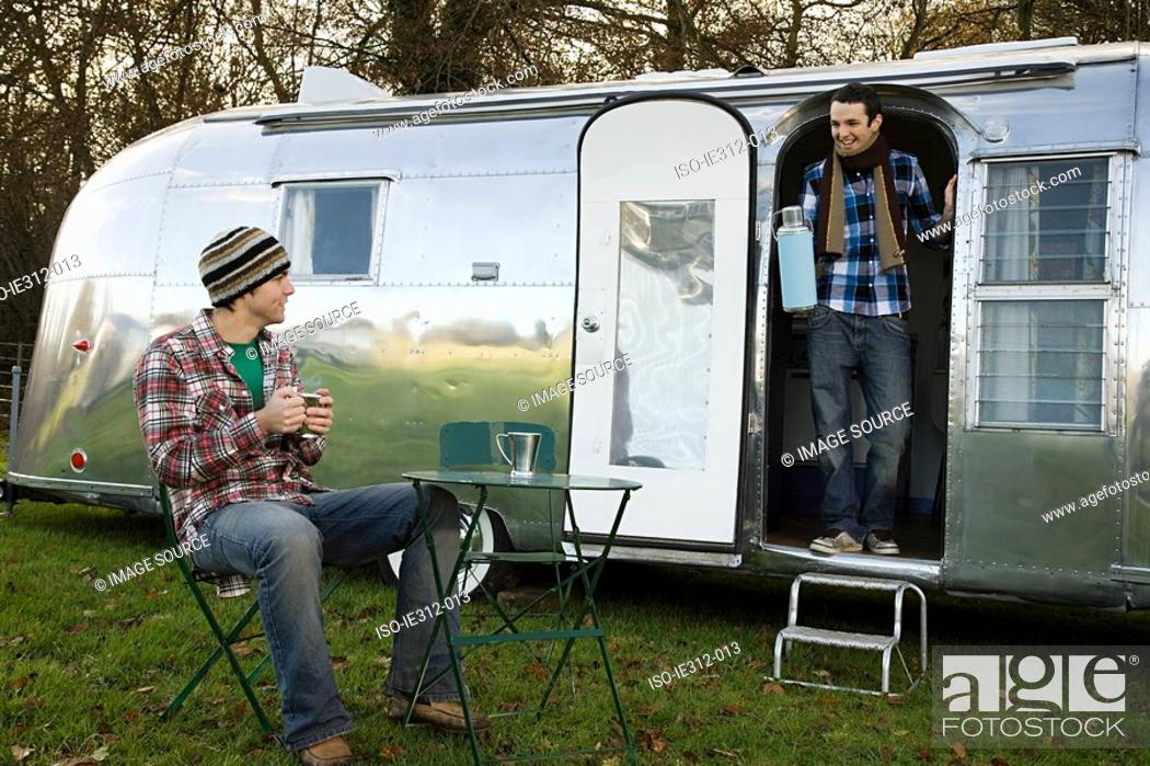Stock Photo: Two teenage boys and a caravan.