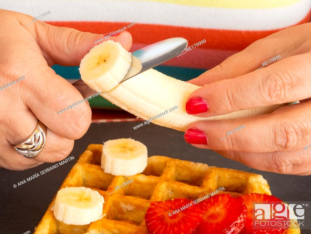 Imagen: A woman with red fingernails cutting strawberry and banana and placing it on a Belgian waffle.