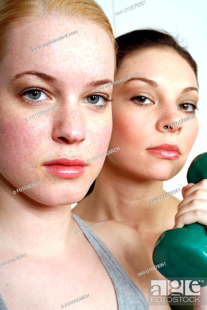 Stock Photo: Two young women with dumbbell.