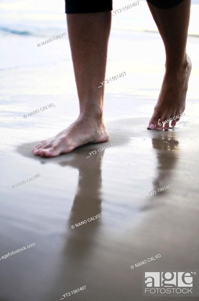 Stock Photo: Young woman walks on the beach at sunset.