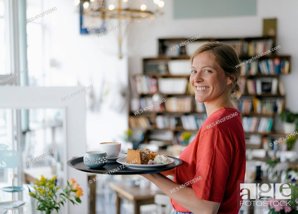 Stock Photo: Portrait of smiling young woman serving coffee and cake in a cafe.