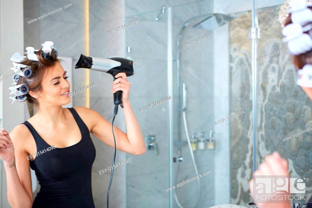 Stock Photo: young woman putting curlers in her hair, bathroom.