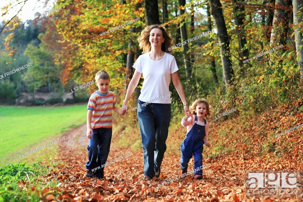 Stock Photo: Mother with daughter and son running hand in hand on path full of leaves in fall, having fun and laughing, autumn foliage covering path in forest, autumn, fall.