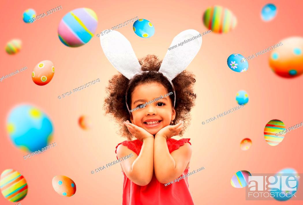 Photo de stock: happy little girl wearing easter bunny ears posing.