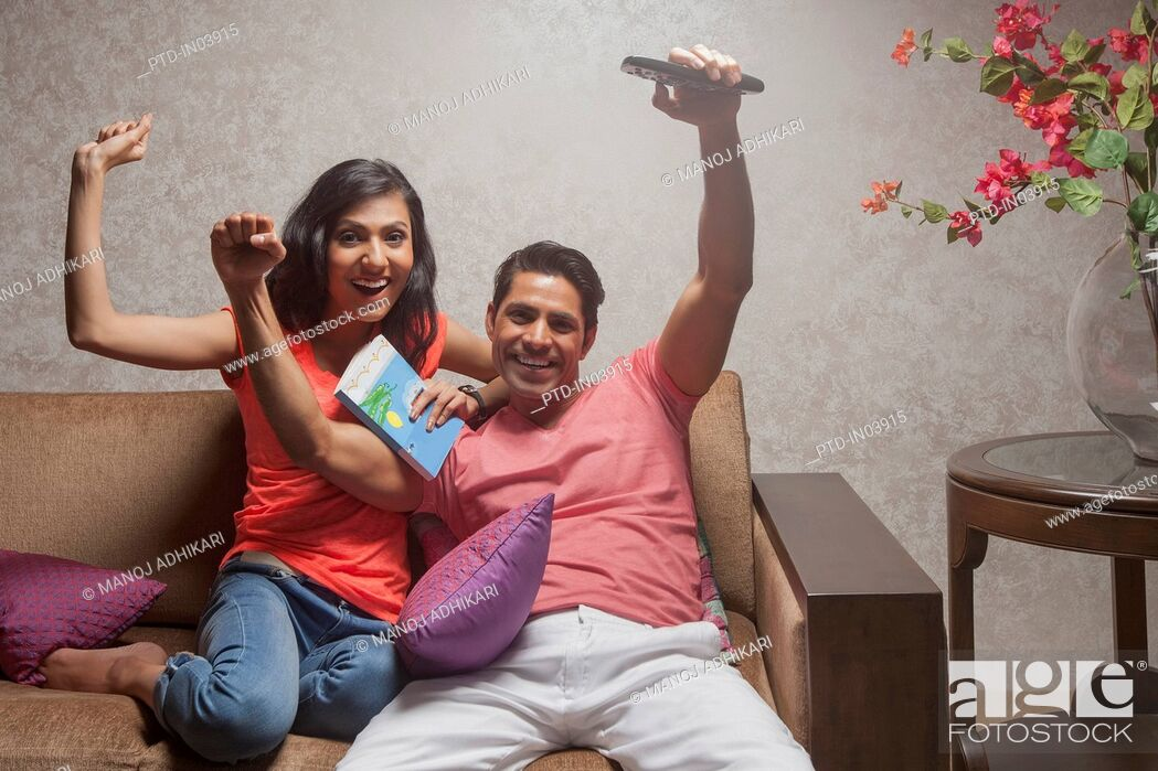 Stock Photo: India, Man and woman watching television with arms raised.