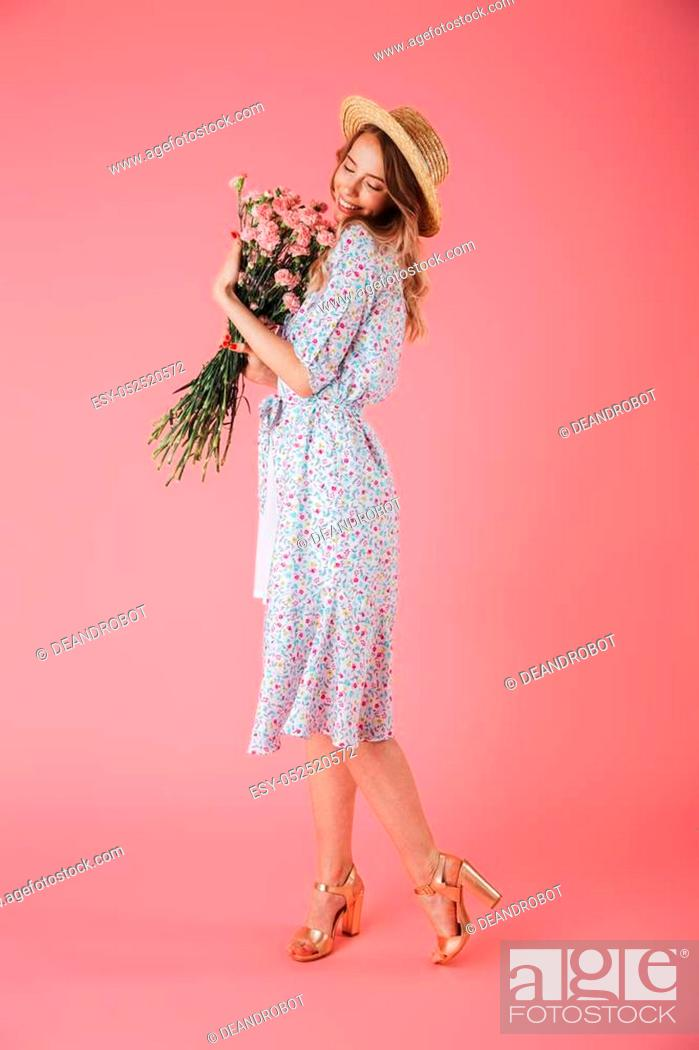 Stock Photo: Full length portrait of a lovely young woman in summer dress and straw hat posing while holding carnations bouquet isolated over pink background.
