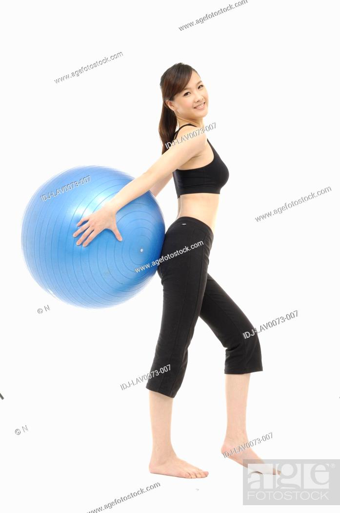 Stock Photo: Beautiful fitness trainer with a ball.