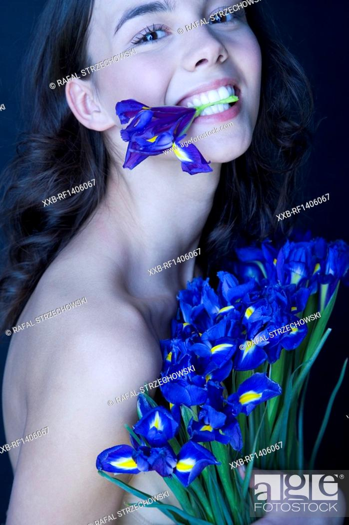Stock Photo: beauty brunette with iris in mouth.