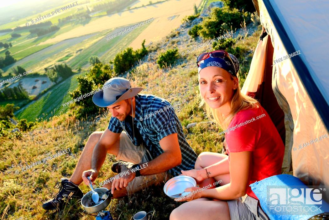 Stock Photo: Young couple in a tent camp on summer outdoor adventure hiking trip.