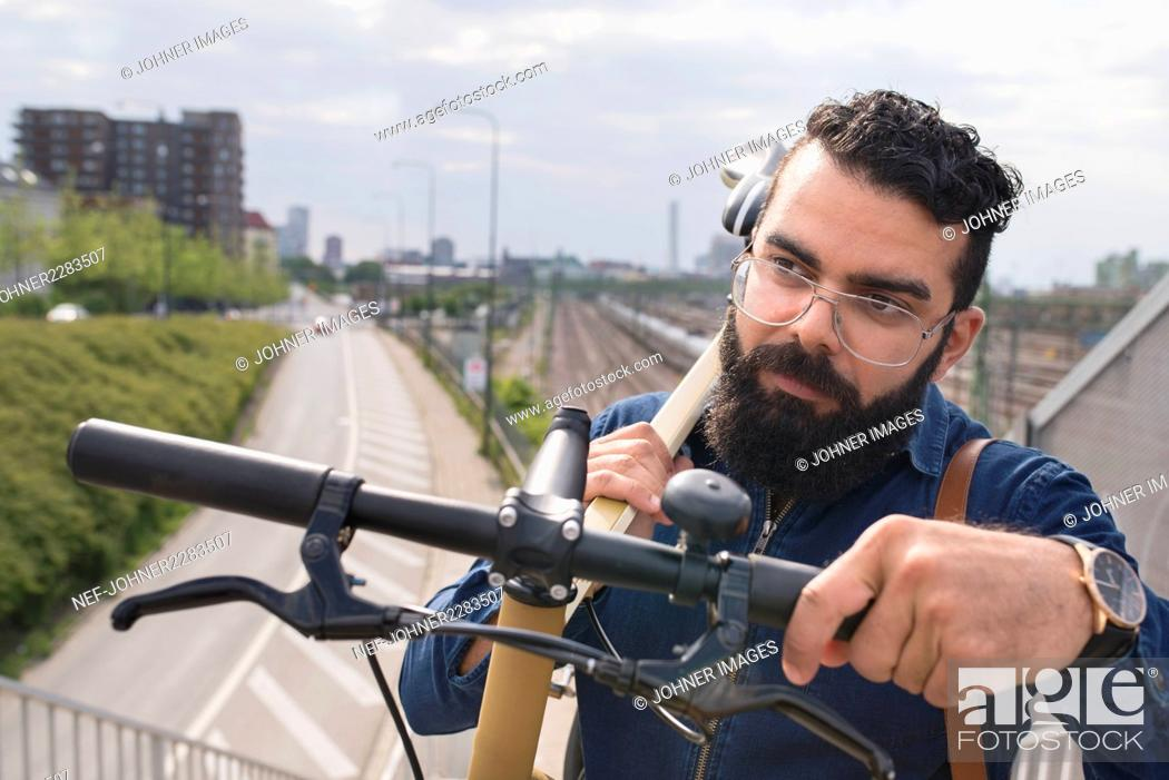 Stock Photo: Bearded man carrying bicycle.